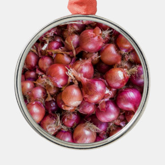 Heap of red onions on market metal ornament