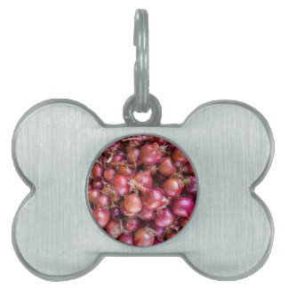 Heap of red onions on market pet ID tag