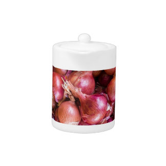 Heap of red onions on market teapot