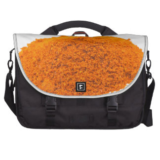Heap of spice cayenne pepper powder on white laptop commuter bag