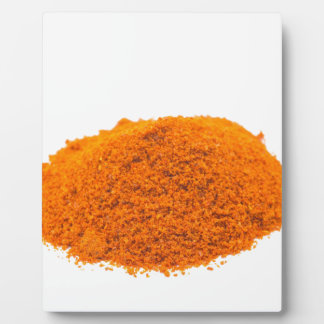 Heap of spice cayenne pepper powder on white plaque