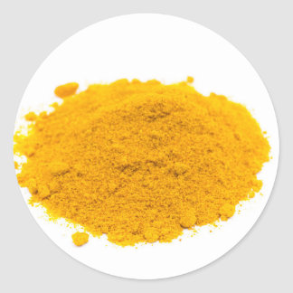 Heap of spice turmeric powder on white background. classic round sticker