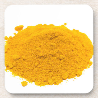 Heap of spice turmeric powder on white background. drink coaster