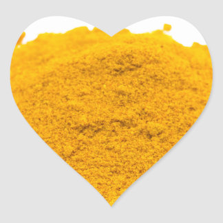 Heap of spice turmeric powder on white background. heart sticker