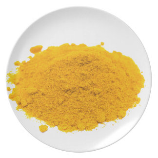 Heap of spice turmeric powder on white background. melamine plate