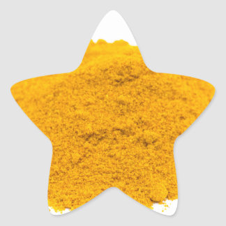 Heap of spice turmeric powder on white background. star sticker