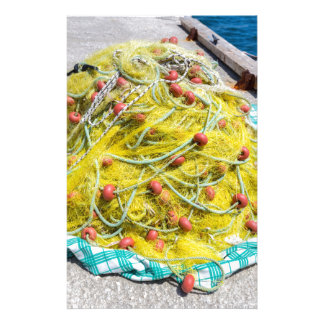 Heap of yellow fishnet on ground at sea stationery