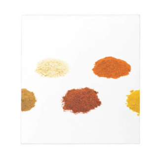 Heaps of several seasoning spices on white notepad