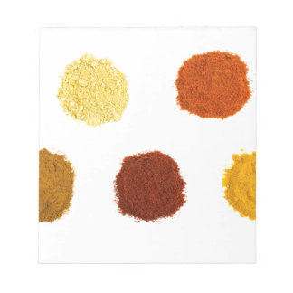 Heaps of various seasoning spices on white notepad