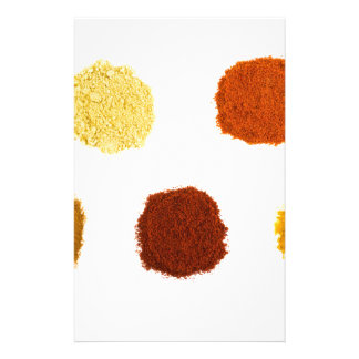 Heaps of various seasoning spices on white stationery