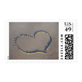 Heart shape drawn in the sand. postage