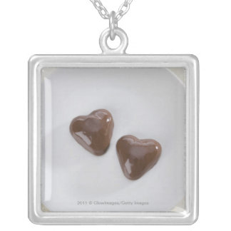 Heart shaped chocolate candies on a plate silver plated necklace