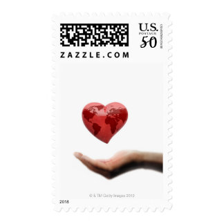 Heart with global map over female hand postage