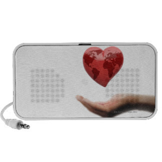 Heart with global map over female hand laptop speakers