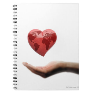 Heart with global map over female hand spiral note book