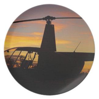 Helicóptero de Robinson R44 en la puesta del sol Plato