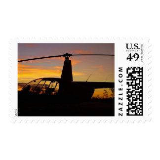 Helicóptero de Robinson R44 en la puesta del sol Sellos
