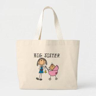 Hermana grande con las camisetas y los regalos de  bolsas