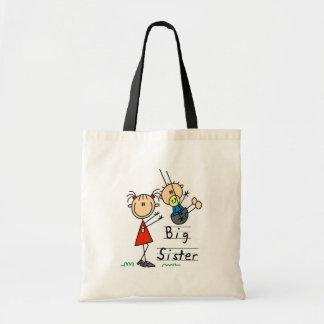 Hermana grande con las camisetas y los regalos de bolsa
