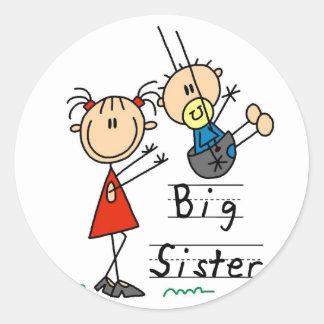 Hermana grande con las camisetas y los regalos de pegatina redonda