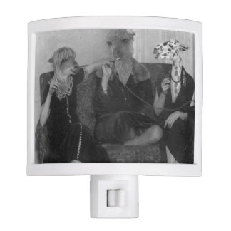 Hermanas de la llama que se sientan en un sofá con lámparas de noche