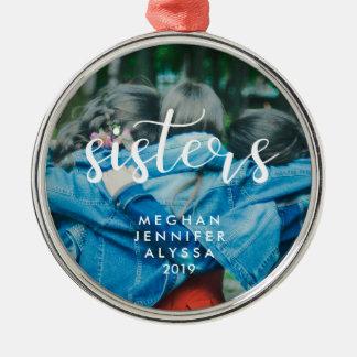 Hermanas modernas simples de la tipografía con la adorno navideño redondo de metal