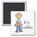 Hermano mayor con las camisetas y los regalos de l imán para frigorífico