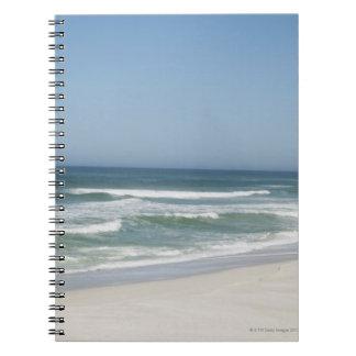 Hermosa vista de la playa contra el cielo claro 2 libros de apuntes con espiral