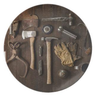 Herramientas viejas en la placa de madera de la plato