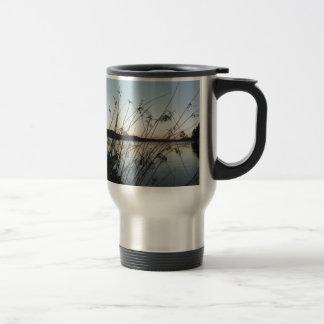 Hierbas en la puesta del sol del lago taza de café