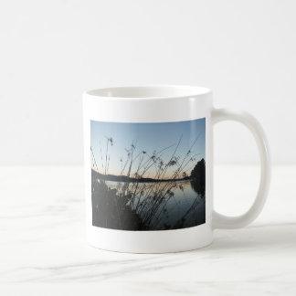 Hierbas en la puesta del sol del lago tazas de café