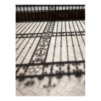 hierro adornado que cerca la sombra en suelo de postal