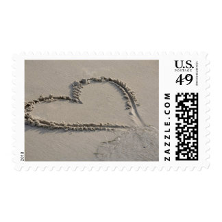 High angle view of a heart shape on the beach stamps