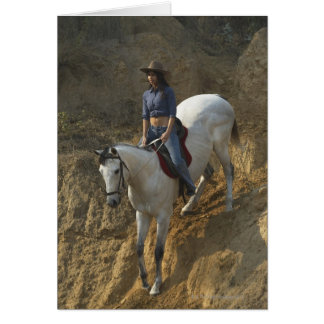 High angle view of a young woman riding a horse card