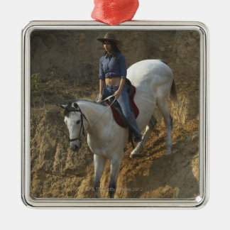 High angle view of a young woman riding a horse metal ornament