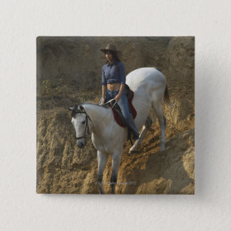 High angle view of a young woman riding a horse pinback button