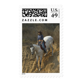 High angle view of a young woman riding a horse stamps