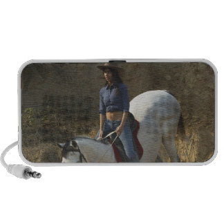 High angle view of a young woman riding a horse mini speakers
