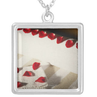 High angle view of rose petals on towels silver plated necklace