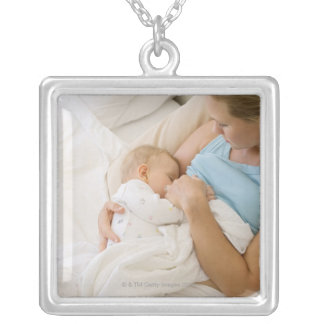 High angle view of woman breastfeeding baby silver plated necklace