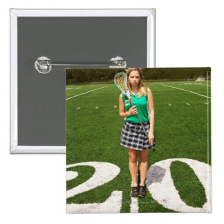 High school lacrosse player (16-18) holding pinback button