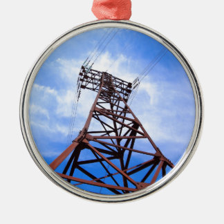 High-voltage tower on blue sky round metal christmas ornament