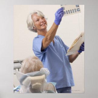 Higienista dental de sexo femenino que examina una poster