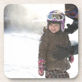 Hija de enseñanza de la madre a la snowboard posavasos de bebida