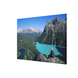 Hiker overlooking turquoise-colored Lake Canvas Print