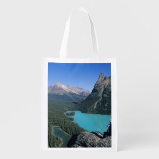 Hiker overlooking turquoise-colored Lake Reusable Grocery Bag