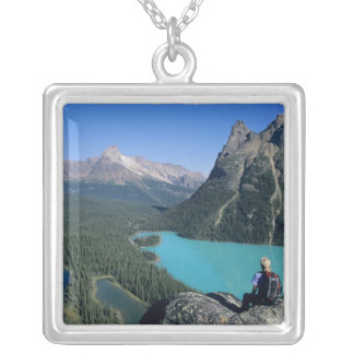 Hiker overlooking turquoise-colored Lake Square Pendant Necklace