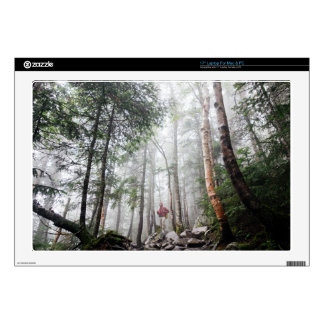 Hiker walks through forest of tall trees skins for laptops