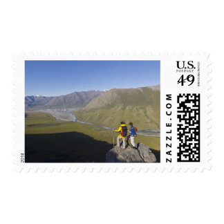 Hikers pausing to admire hill scenery postage stamp