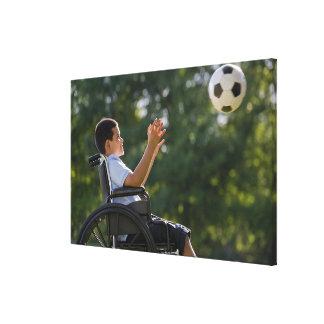 Hispanic boy, 8, in wheelchair with soccer ball canvas print